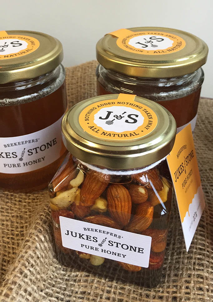 Jukes and Stone 227g honey jars with with mixed nuts placed on a hessian cloth for display