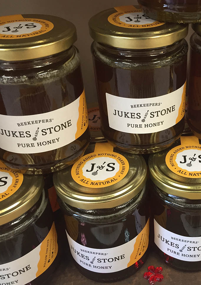 Jukes and Stone honey jars stacked on a shelf